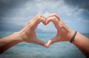 Twee handen die samen een hartje vormen in de lucht.